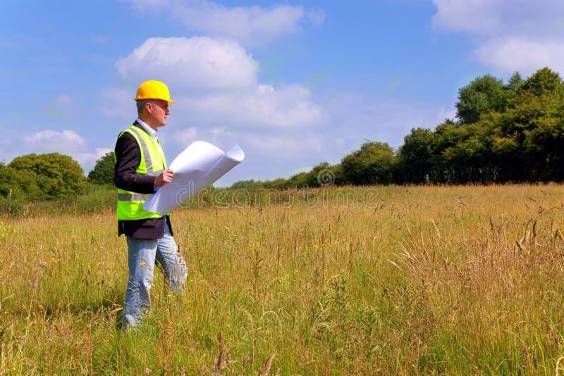 Architect die een nieuw bouwterrein onderzoekt stock afbeelding
