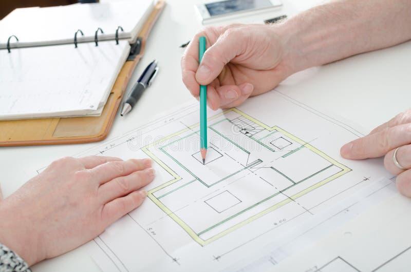 Architect die huisplannen tonen stock fotografie