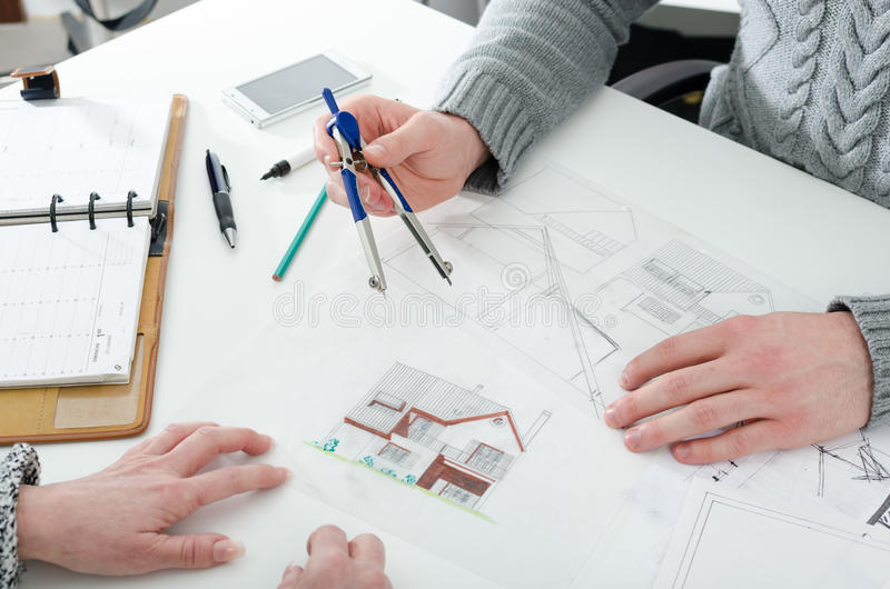Architect die huisplannen tonen stock afbeelding