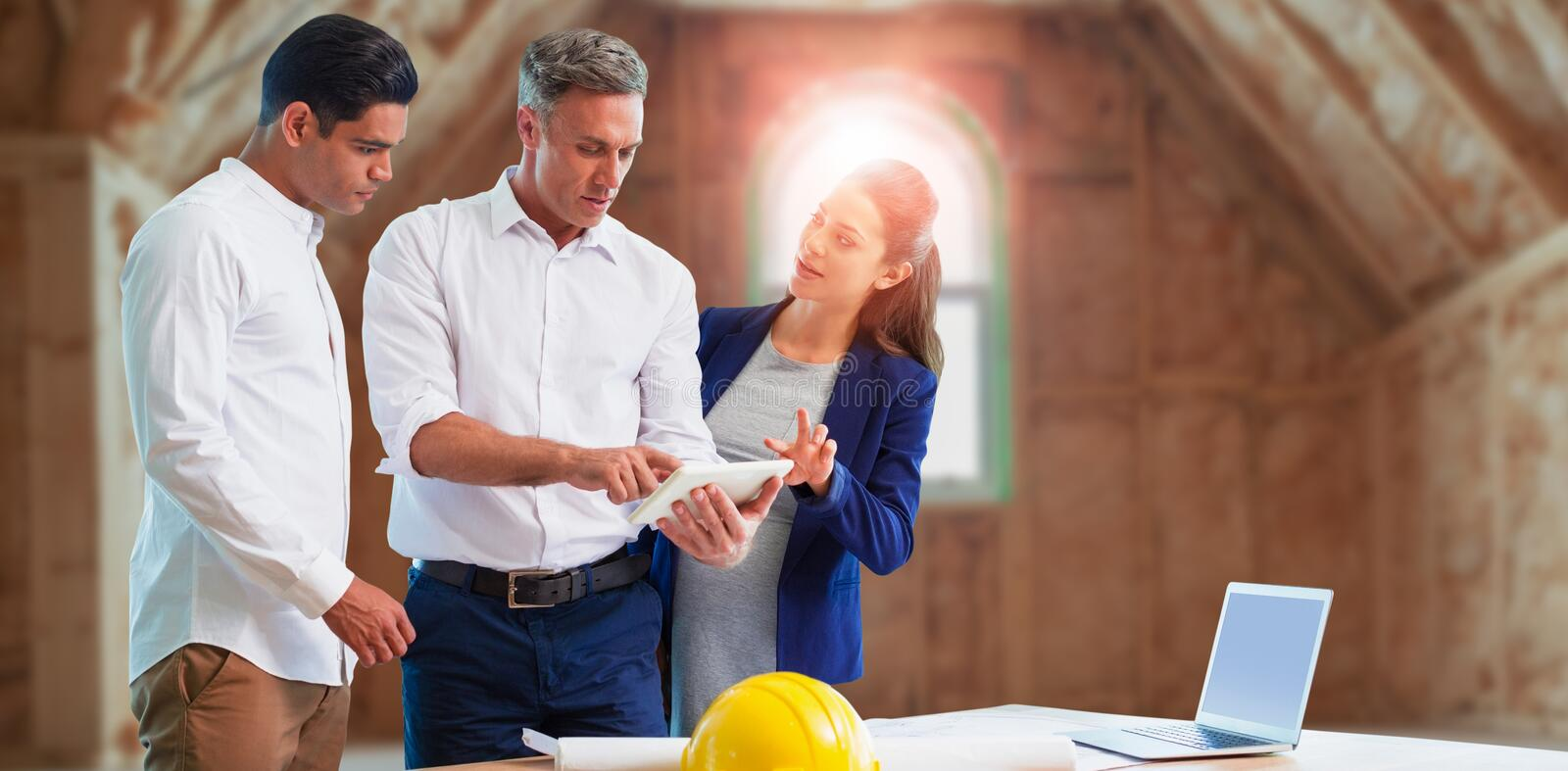Composite image of architect discussing over tablet computer royalty free stock images