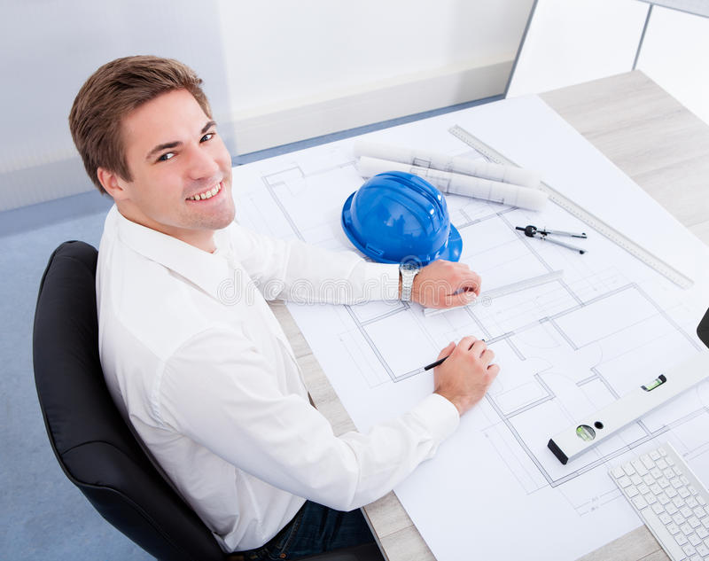 Architect Drawing On Blueprint. Portrait Of A Young Architect Drawing Plan On Blueprint royalty free stock photos