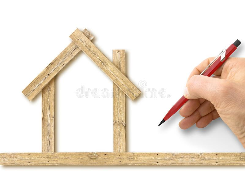 Architect drawing a conceptual wooden house on white background - concept image.  stock photo