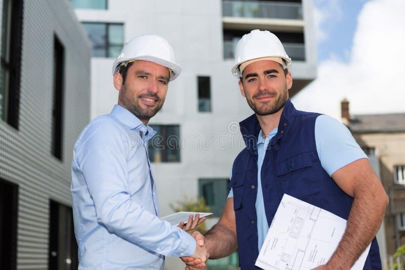 Architect en arbeidershandenschudden op bouwwerf royalty-vrije stock afbeelding