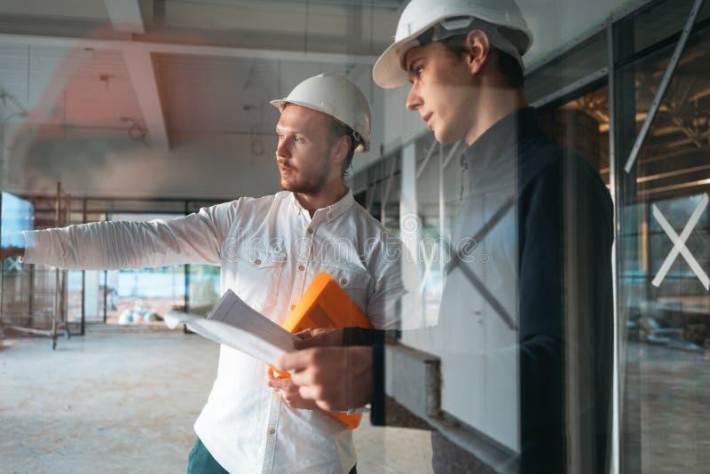 Architect en bouwwerktuigkundige bespreken projecttekening stock afbeeldingen