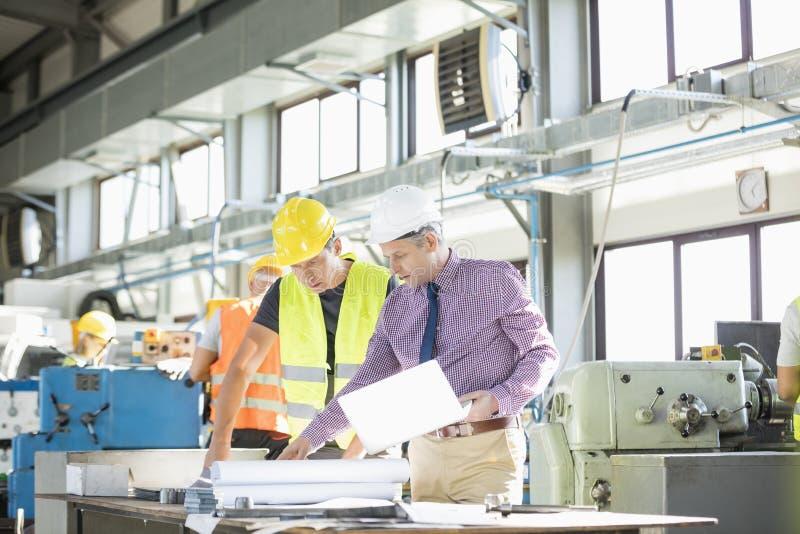 Architect en handarbeider die blauwdruk onderzoeken bij lijst in de industrie stock foto's