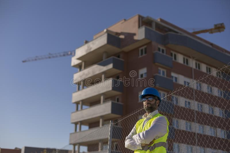 Architect or Engineer on the Construction Site. Daytime. Wearing protection equipment royalty free stock image