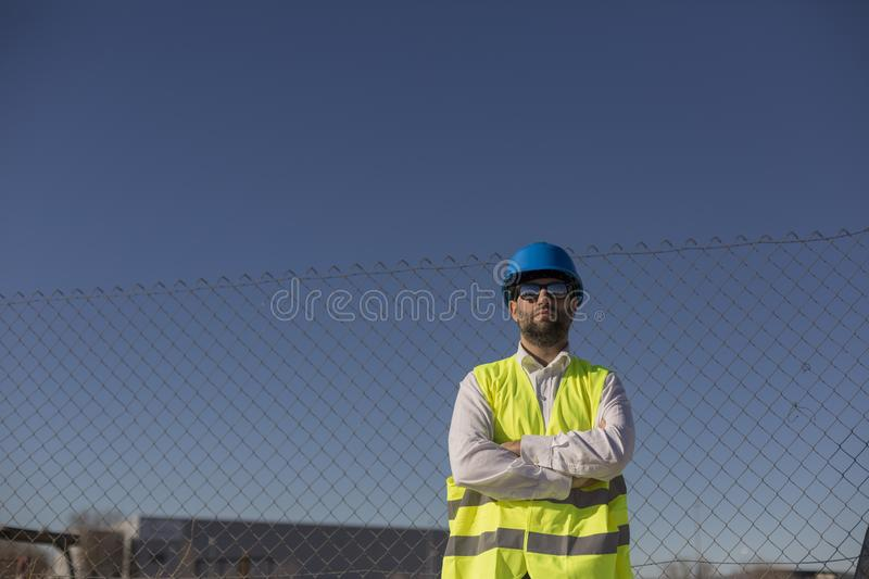 Architect or Engineer on the Construction Site. Daytime. Wearing protection equipment royalty free stock photography