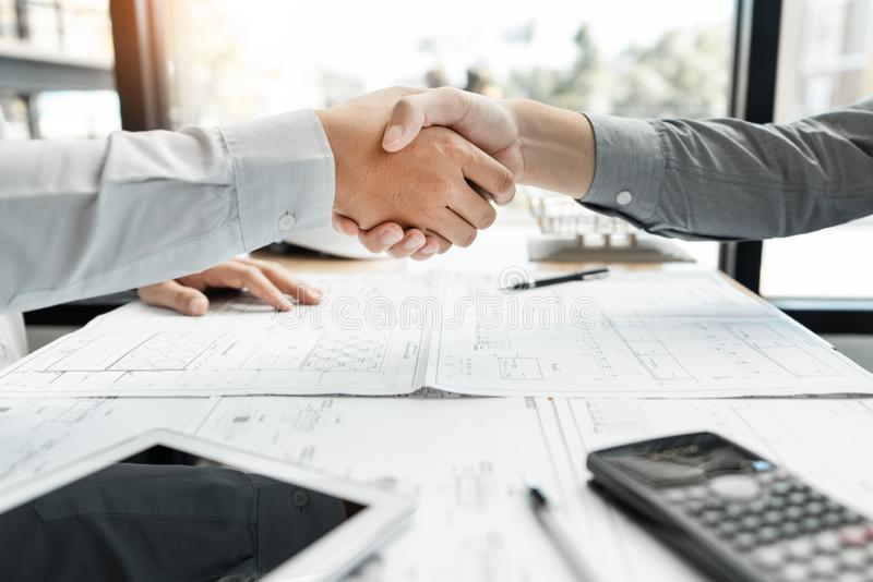 Architect and engineer construction workers shaking hands while working for teamwork and cooperation concept after finish an agree royalty free stock image