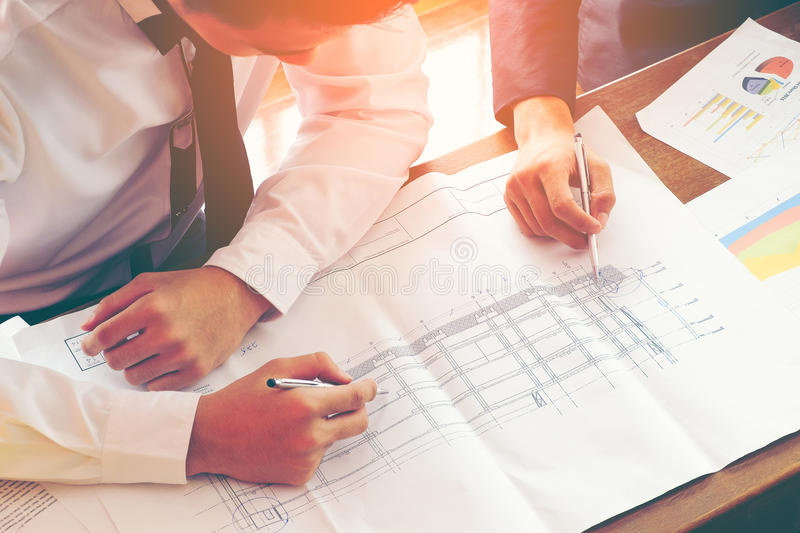 Architect and engineer discuss with blue print construction drawing on wood table royalty free stock images