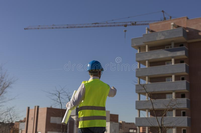 Architect or Engineer holding blueprints on the Construction Site. Daytime. Wearing protection equipment royalty free stock image