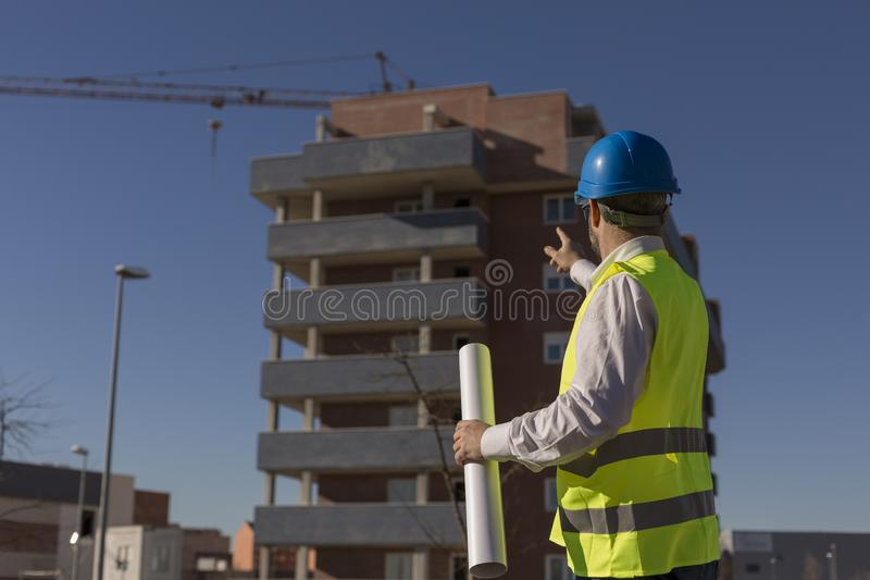 Architect or Engineer holding blueprints on the Construction Site. Daytime. Wearing protection equipment stock image