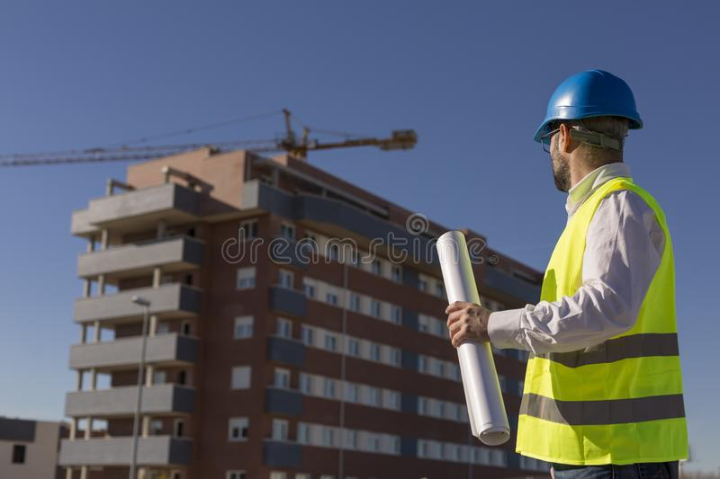 Architect or Engineer holding blueprints on the Construction Site. Daytime. Wearing protection equipment royalty free stock images