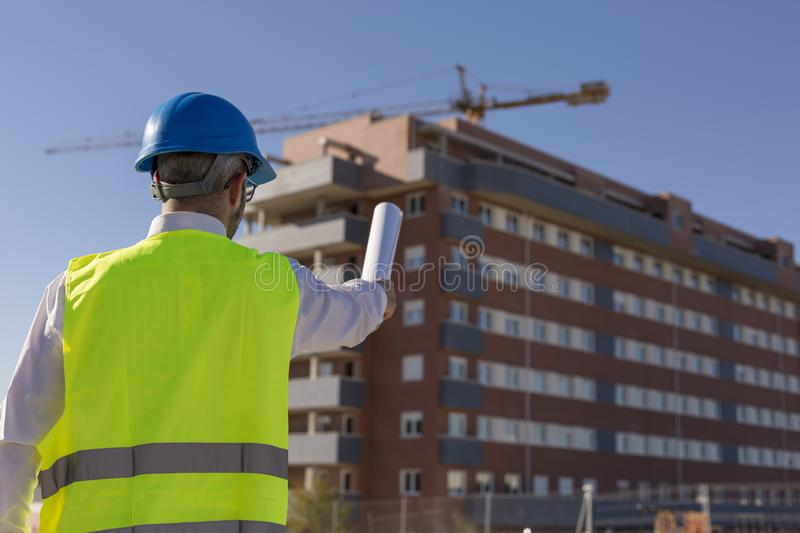 Architect or Engineer holding blueprints on the Construction Site. Daytime. Wearing protection equipment stock photo