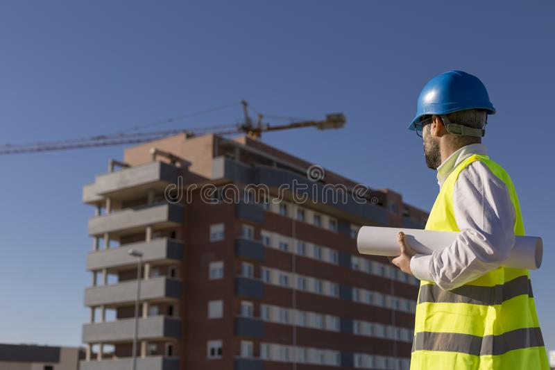 Architect or Engineer holding blueprints on the Construction Site. Daytime. Wearing protection equipment royalty free stock photos