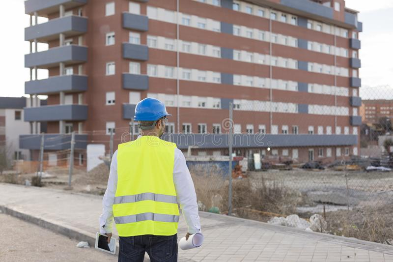 Architect or Engineer man holding blueprints and tablet on the Construction Site. Wearing protection clothes. Crane on background royalty free stock photo