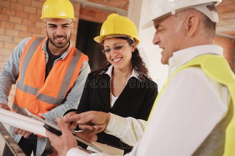 Architect Engineer And Manual Worker Meeting In Construction Site stock photography
