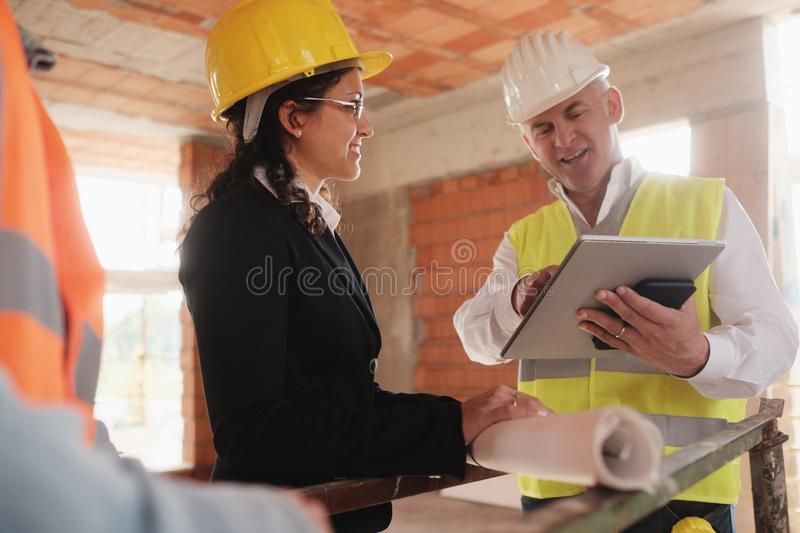 Architect Engineer And Manual Worker Meeting In Construction Site royalty free stock image