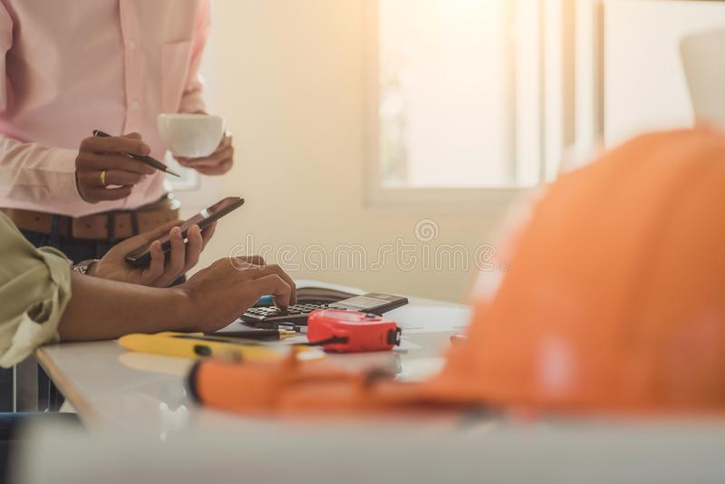 Architect or engineer reading message on phone during the meeting building plan design project in office. Construction engineering. Tools and structure team stock photography