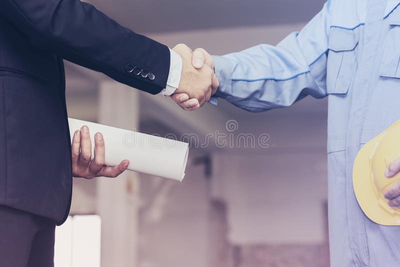 Architect engineer shaking hands with businessman on site stock photo