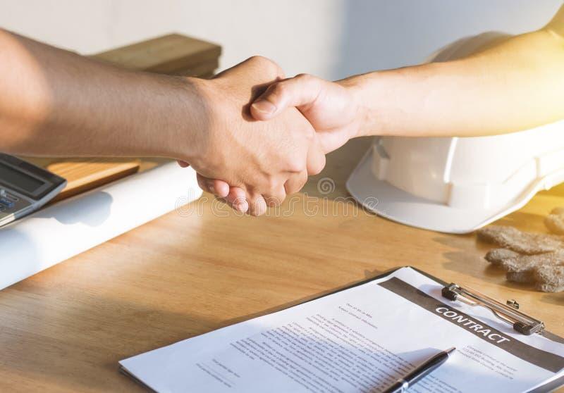 Architect engineer shaking hands with investor finishing signing stock image
