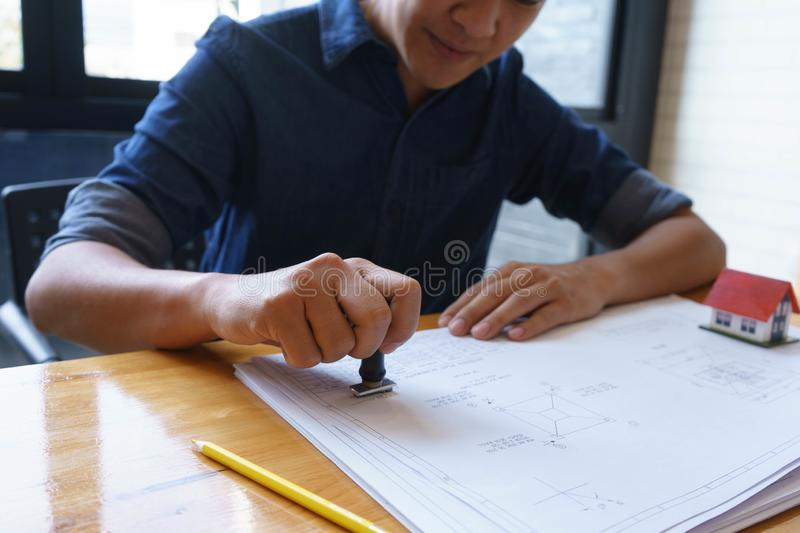 Architect or engineer stamping the document or blueprint on wooden desk - architectural project, Construction concept royalty free stock image