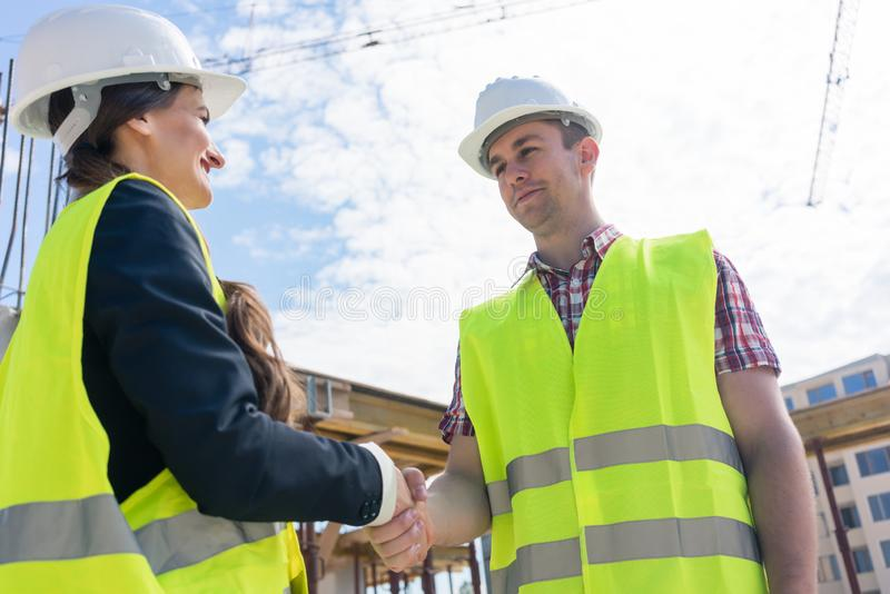 Architect and engineer or supervisor shaking hands on the construction site royalty free stock images