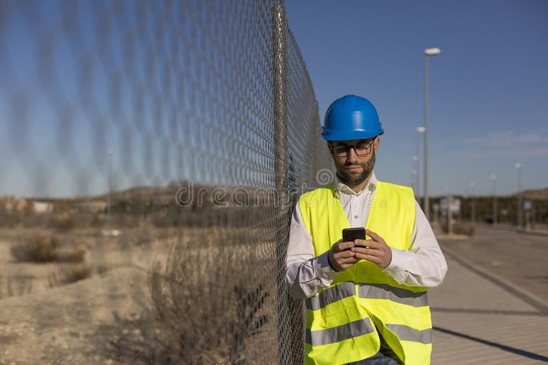 Architect or Engineer using Cell Phone on the Construction Site stock photography