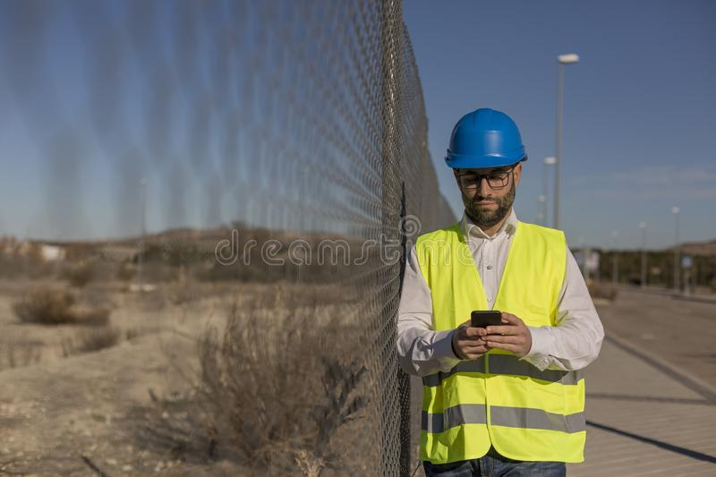 Architect or Engineer using mobile Phone on the Construction Site. Daytime. Wearing protection equipment royalty free stock image