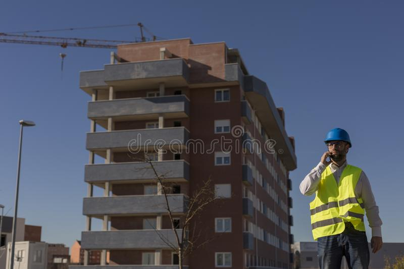 Architect or Engineer using mobile Phone on the Construction Site. holding blueprints Daytime. Wearing protection equipment royalty free stock photo