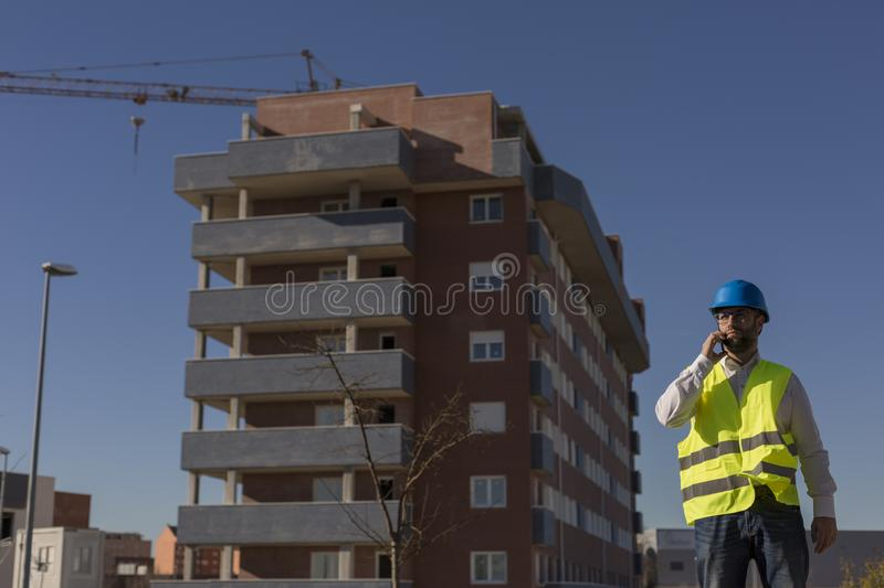Architect or Engineer using mobile Phone on the Construction Site. holding blueprints Daytime. Wearing protection equipment stock images