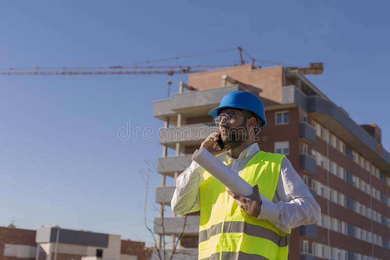 Architect or Engineer using mobile Phone on the Construction Site. holding blueprints Daytime. Wearing protection equipment royalty free stock photos