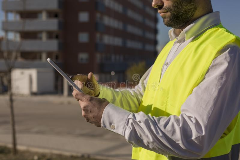 Architect or Engineer using tablet on the Construction Site. Daytime. Wearing protection equipment royalty free stock images