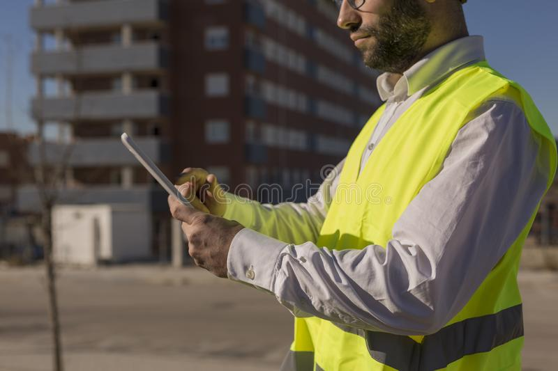 Architect or Engineer using tablet on the Construction Site. Daytime. Wearing protection equipment stock photography