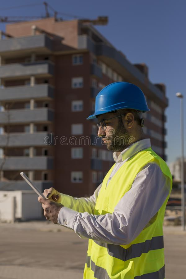 Architect or Engineer using tablet on the Construction Site. Daytime. Wearing protection equipment stock photos