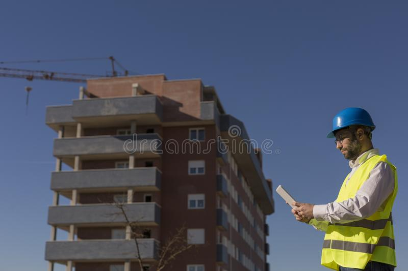 Architect or Engineer using tablet on the Construction Site. Daytime. Wearing protection equipment royalty free stock photo