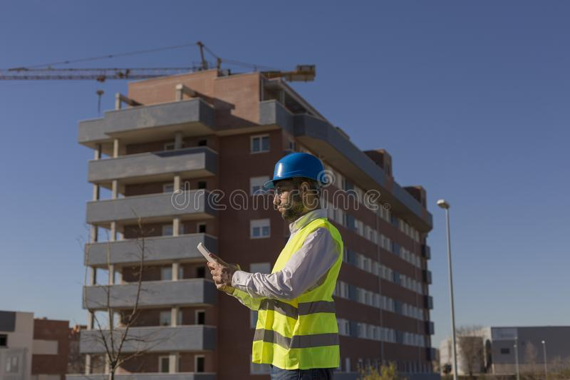 Architect or Engineer using tablet on the Construction Site. Daytime. Wearing protection equipment stock photo