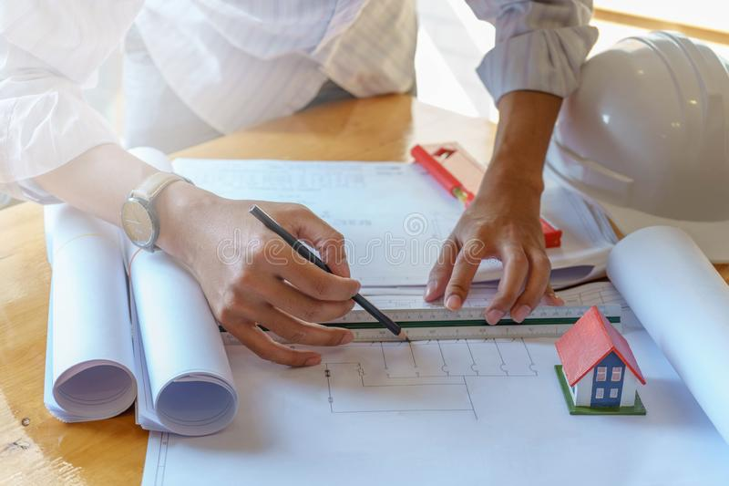 Architect or engineer working on blueprint at workplace on wooden desk. - architectural project, Construction concept royalty free stock photo