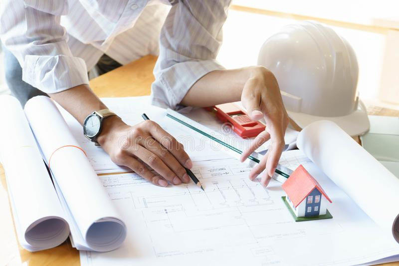 Architect or engineer working on blueprint at workplace on wooden desk. - architectural project, Construction concept royalty free stock photography