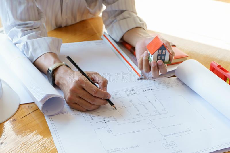 Architect or engineer working on blueprint at workplace on wooden desk. - architectural project, Construction concept royalty free stock photos