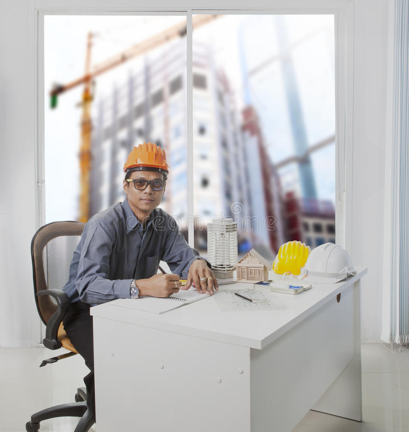 architect engineer working in office room against building construction through mirror window use for architecture and stock photo