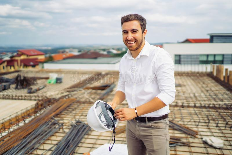 architect engineer working and smiling on construction with hardhat in hand stock image