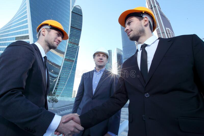 Architects shaking hands at construction site stock image