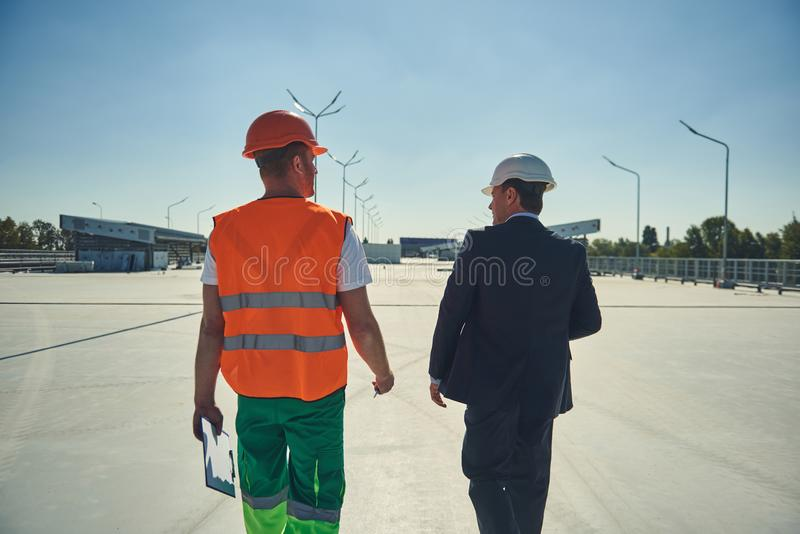 Architect and foreman are going on construction site. Back veiw of project manager and engineer are locating on building site royalty free stock image