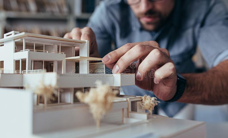 Architect hands making model house. Close up of male architect hands making model house. Man architect working in the office stock photography