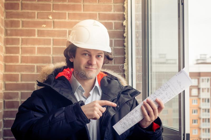 Architect in hardhat, holding blueprints smiling look at the camera and points his finger to the drawing. Soft focus royalty free stock photo