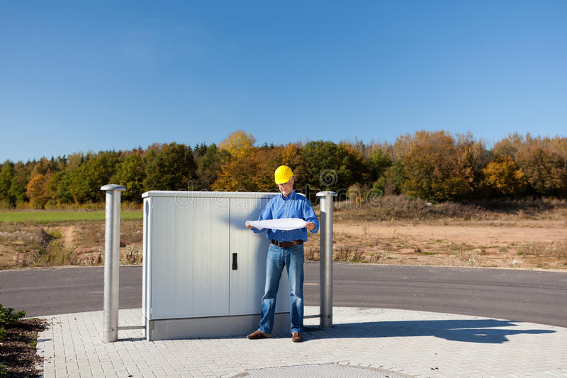 Architect Holding Blueprint While Standing Against Electric Box royalty free stock photography