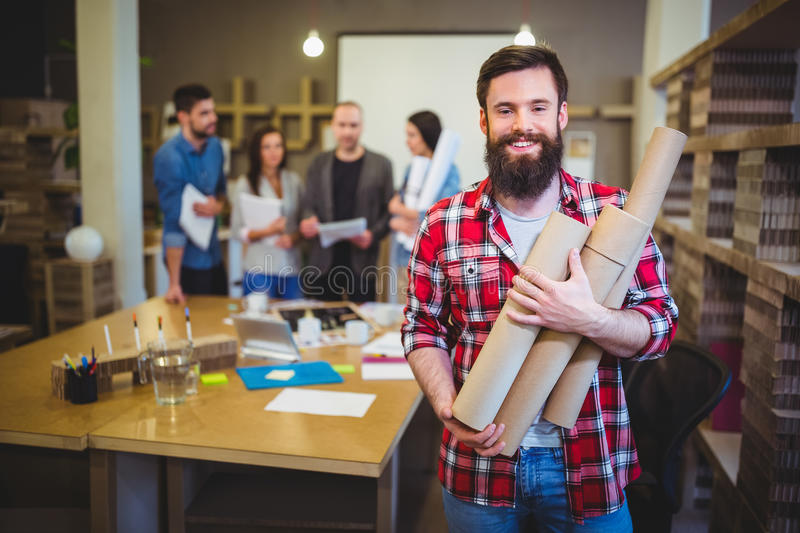 Architect holding blueprint tubes while standing by table stock download architect holding blueprint tubes while standing by table stock photo image of checked malvernweather Image collections