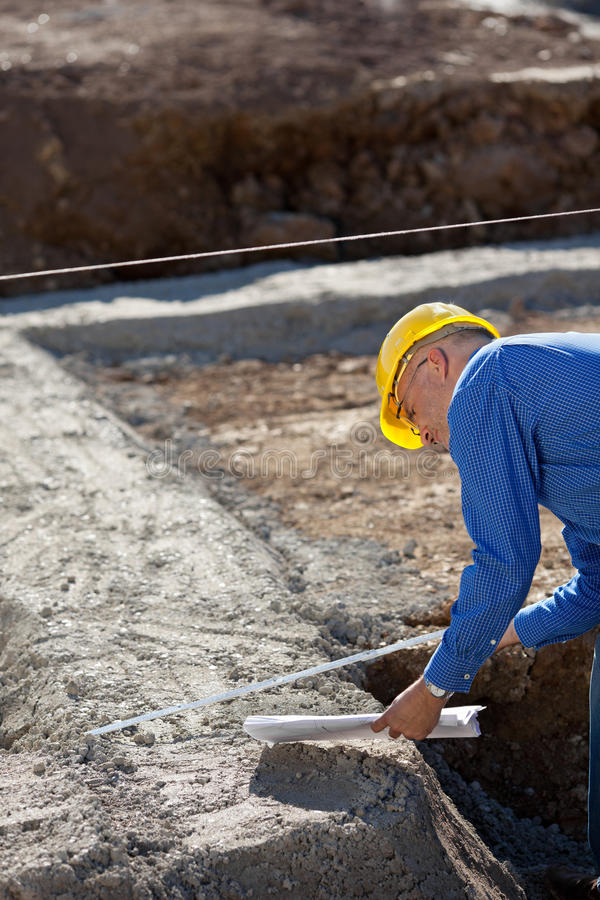 Download Architect Holding Blueprint While Using Measuring Tape At Constr Stock Photos - Image: 31207143