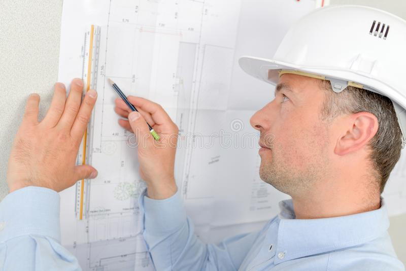Architect holding plans up to wall royalty free stock photography