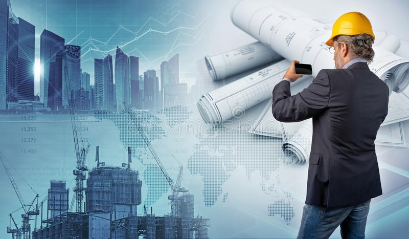 Architect holding a smartphone and blueprints in urban background stock photos